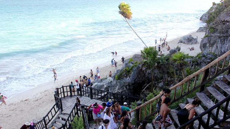 In this Jan. 4, 2013, photograph, a line of people leave the swimming beach next to the Mayan ruins in Tulum, Mexico. Tulum may be best-known for its ancient Mayan ruins, which attract a steady stream of day-trippers, cruise passengers and tour buses. The complex of crumbling structures here is smaller and less impressive than some other Mayan sites like Chichen Itza, but its location atop seaside cliffs is one of the most scenic ruin sites on the Yucatan. (AP Photo/Manuel Valdes)