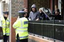 Police officers stand outside a block of flats in Greenwich following a raid in connection with the killing of a British soldier in nearby Woolwich, south east London
