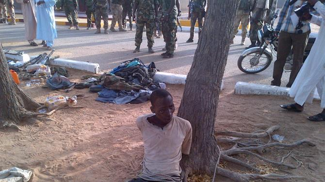 In this photo taken with a mobile phone, Tuesday, May. 7, 2013,  Bakura Ibrahim, a suspected member of Islamic extremist group arrested by soldiers is tied to a tree in Bama, Nigeria. Coordinated attacks by Islamic extremists armed with heavy machine guns killed at least 42 people in northeast Nigeria, authorities said Tuesday, the latest in a string of increasingly bloody attacks threatening peace in Africa's most populous nation. The attack struck multiple locations in the hard-hit town of Bama in Nigeria's Borno state, where shootings and bombings have continued unstopped since an insurgency began there in 2010. Fighters raided a federal prison during their assault as well, freeing 105 inmates in another mass prison break to hit the country, officials said. (AP Photo/Abdukareem Haruna)
