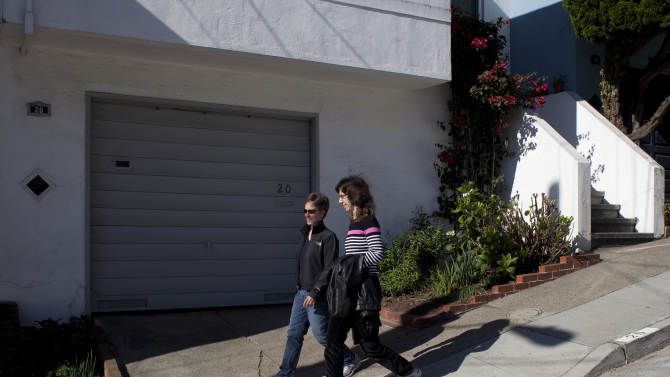 In this photo taken Monday, Nov. 12, 2012, Amy Cunninghis, left, and Karen Golinski, right, walk down a street near their home in San Francisco. All Golinski wanted was to enroll her spouse in her employer-sponsored health plan. Four years later, her request still is being debated. Because Golinski is married to another woman and she works for the federal government, her personal personnel problem has morphed into a multi-pronged legal attack by gay rights activists to overturn the 1996 law that defines marriage as the union of a man and a woman. (AP Photo/Eric Risberg)
