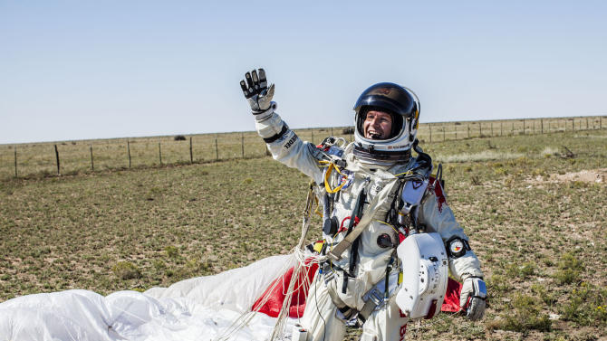 In this photo provided by Red Bull Stratos, Pilot Felix Baumgartner of Austria celebrates after successfully completing the final manned flight for Red Bull Stratos in Roswell, N.M., Sunday, Oct. 14, 2012. Baumgartner came down safely in the eastern New Mexico desert minutes about nine minutes after jumping from his capsule 128,097 feet, or roughly 24 miles, above Earth. (AP Photo/Red Bull Stratos, Balazs Gardi)