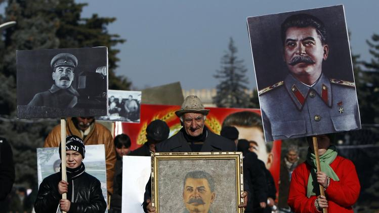 People carry portraits of late Soviet dictator Josef Stalin as they attend a gathering marking the 130th anniversary of his birthday in Stalin's hometown town of Gori