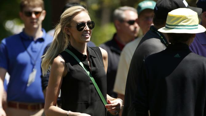 Paulina Gretzky follows her fiance Dustin Johnson as he plays during the first round of the 2014 Masters golf tournament at the Augusta National Golf Club in Augusta
