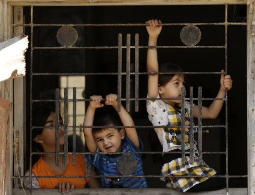 Palestinian children watch a funeral in Gaza