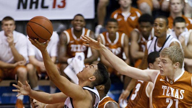 Chaminade forward Kevin Hu (23) drives to the basket as Texas forward Connor Lammert (21) defends during the first half of an NCAA college basketball game Monday, Nov. 19, 2012, in Lahaina, Hawaii. (AP Photo/Eugene Tanner)