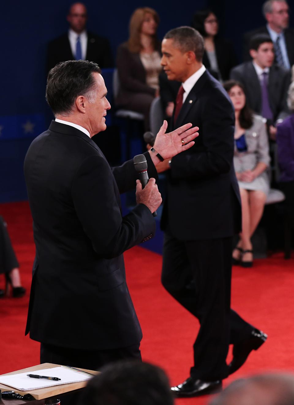 President Barack Obama, right, walks past as Republican presidential nominee Mitt Romney members of the audience during the second presidential debate at Hofstra University, Tuesday, Oct. 16, 2012, in Hempstead, N.Y. (AP Photo/Pool-Win McNamee)