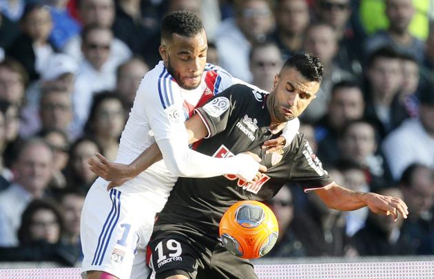 Olympique Lyon's Lacazette challenges Obbadi of Monaco during their French Ligue 1 soccer match at the Gerland stadium