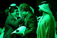 UEFA president Michel Platini (C) hugs Argentinian football icon and former player Diego Maradona (L) during the first session of the International Sports Conference in Dubai on December 28, 2012. Platini renewed his call on Thursday for the 2022 World Cup in Qatar to be switched to the winter to avoid the crushing heat of a Gulf summer and shared with neighbouring countries