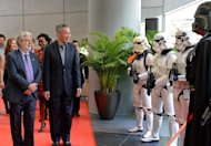 George Lucas (left) and Singapore's Prime Minister Lee Hsien Loong (2nd L) review Stormtroopers at the opening of Lucasfilm's new production facility, the Sandcrawler in Singapore on January 16, 2014