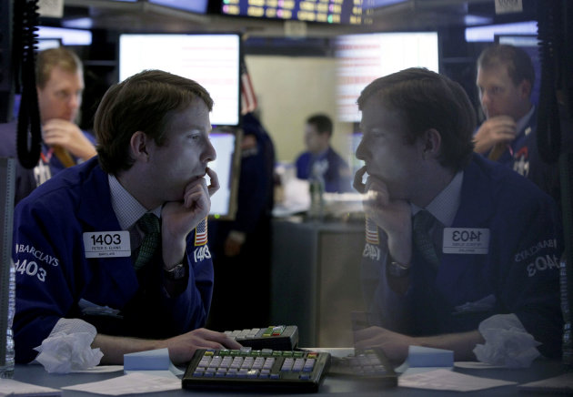 FILE - In this Tuesday, Oct. 23, 2012 file photo, specialist Peter Elkins, foreground, is reflected in a trading post monitor as he works on the floor of the New York Stock Exchange, in New York. If W