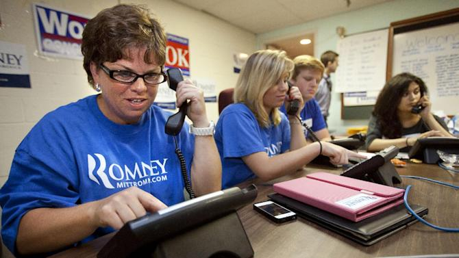 In this photo taken June 29, 2012, Karen Chew, left, of Washington, and fellow volunteers make phone calls for the Romney campaign at a Romney Victory Office in Fairfaix, Va. where she says she puts in about a dozen hours a week but wishes she could put in more time. Call them passionate, idealistic, earnest, even a tad naive: The volunteers helping to power the Obama and Romney campaigns are outliers at a time when polls show record low public satisfaction with government and a growing belief that Washington isn't on their side.  While motivated by opposing goals, the Obama and Romney volunteers share at least one key trait: an abiding faith in the political process and a belief that it still matters who occupies the White House.  (AP Photo/Jacquelyn Martin)