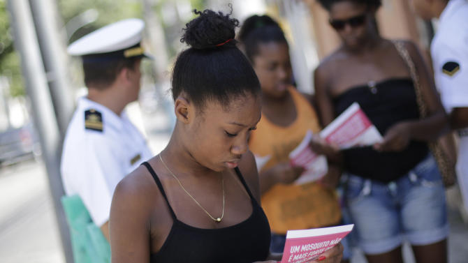 A woman reads a pamphlet distributed by navy sailors, in Rio de Janeiro, Brazil, Saturday, Feb. 13, 2016. More than 200,000 army, navy and air force troops are fanning out across Brazil to show people how to eliminate the Aedes aegypti mosquito that spreads the Zika virus, which many health officials believe is linked to severe birth defects.The nationwide offensive is part of President Dilma Rousseff's declared war on the virus that has quickly spread across the Americas.(AP Photo/Silvia Izquierdo)