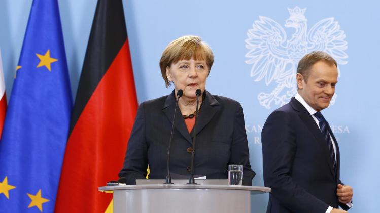 German Chancellor Merkel prepares to address to media as Polish PM Tusk looks on after their meeting in Warsaw