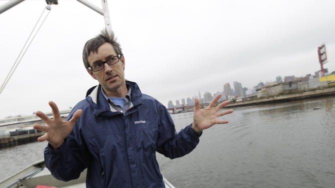In this Oct. 24, 2012 photo Phillip Musegaas, an environmental lawyer for Riverkeeper, leads a boat tour of Newtown Creek in New York. Just across the East River from Manhattan, within sight of the United Nations and shimmering midtown skyscrapers, tens of millions of gallons of pollution are awaiting cleanup in a neighborhood where working-class families have lived for generations and wealthier ones are moving in. Newtown Creek straddling Brooklyn and Queens is home to a federal Superfund site the size of 55 football fields. (AP Photo/Mary Altaffer)