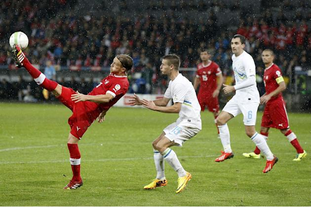 Switzerland's Michael Lang, left, fights for the ball with Slovenia's Andraz Struna during the FIFA World Cup 2014 group E qualifying soccer match between Switzerland and Slovenia at the Stade de Suis