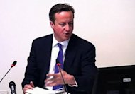 "A video grab from footage taken inside the Leveson Inquiry shows British Prime Minister David Cameron giving evidence at the Leveson Inquiry into press ethics at the High Court in London. Cameron received a text message from Murdoch's British newspaper boss saying they were ""in this together"", a press ethics inquiry heard during testimony from the prime minister"