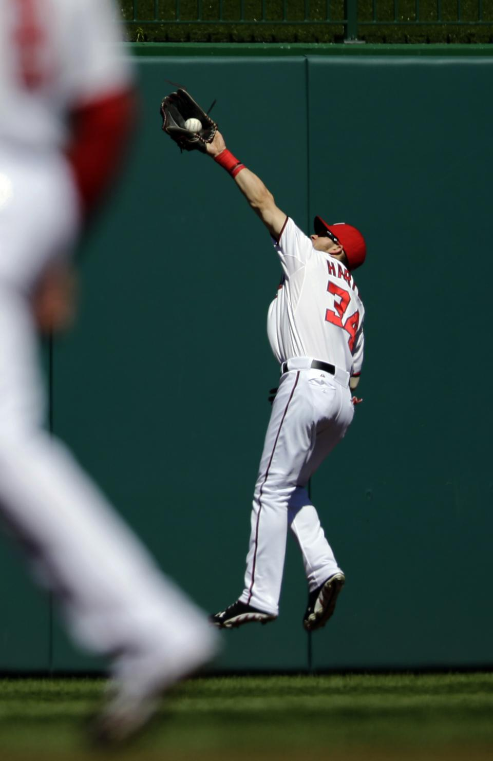 Washington Nationals center fielder Bryce Harper jumps to catch a fly hit by Milwaukee Brewers' Aramis Ramirez during the first inning of a baseball game at Nationals Park, Monday, Sept. 24, 2012, in Washington. (AP Photo/Alex Brandon)
