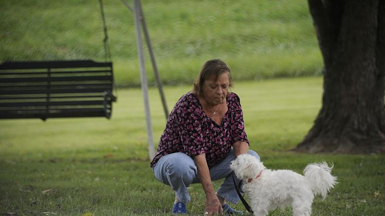 CORRECTS TYPE OF MENINGITIS TO FUNGAL INSTEAD OF BACTERIAL - Patsy Bivins, 68 of Sturgis, Ky., kneels down while walking her dog Little Britches at her apartment in Sturgis, Ky., Friday, October 5, 2012. Bivins was injected with steroids at St. Mary Sugricare in Evansville, Ind., who notified her of possibly being infected with fungal Meningitis. (AP Photo/Stephen Lance Dennee)