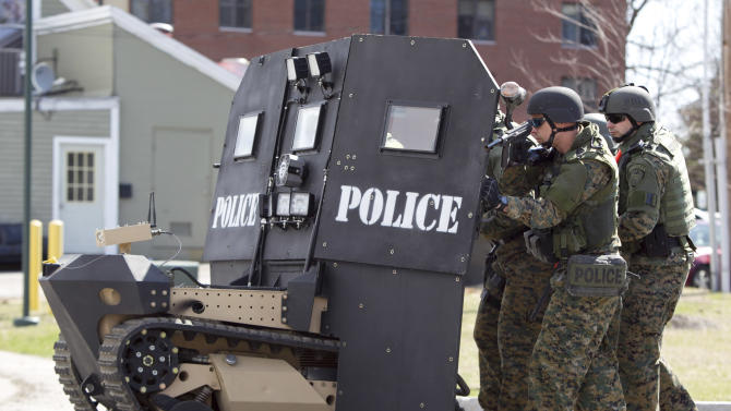 A SWAT robot, a remote-controlled small tank-like vehicle with a shield for officers, is demonstrated for the media in Sanford, Maine on Thursday, April 18, 2013. Howe & Howe Technologies, a Waterboro, Maine company, says their device keeps SWAT teams and other first responders safe in standoffs and while confronting armed suspects. Police now typically use hand-held shields when storming a building. (AP Photo/Robert F. Bukaty)