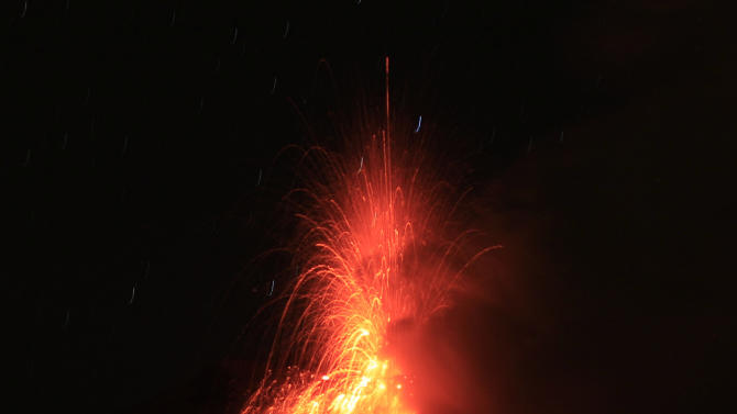 Lava erupts from the Tungurahua volcano, seen from Huambalo, Ecuador, early Tuesday, Aug. 21, 2012. (AP Photo/Dolores Ochoa)