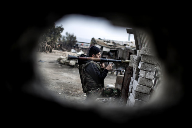 A Free Syrian Army fighter holds his weapon during heavy clashes with government forces in Aleppo, Syria, Sunday, Jan. 20, 2013. The revolt against President Bashar Assad began in March 2011with peaceful protests but morphed into a civil war that has killed more than 60,000 people, according to a recent United Nations recent estimate. (AP Photo/Andoni Lubaki)