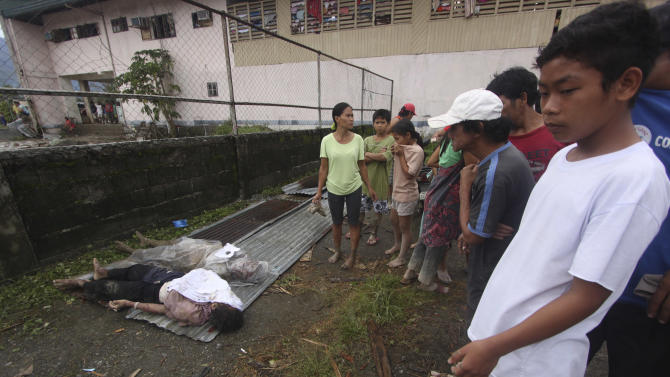 Residents look at bodies recovered from flashflood in New Bataan, Compostela Valley province, southern Philippines on Wednesday Dec. 5, 2012. The death toll from Typhoon Bhopa climbed to more than 100 people Wednesday, while scores of others remain missing in the worst-hit areas of the southern Philippines. (AP Photo/Karlos Manlupig)