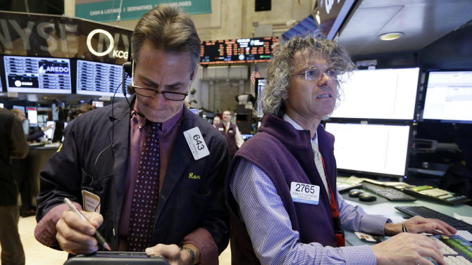 Trader Ronald Madarasz, left, and specialist Donald Civitanova work on the floor of the New York Stock Exchange Thursday, April 10, 2014. U.S. stock indexes are slipping lower in early trading Thursday as investors pick over a mixed batch of corporate earnings reports. (AP Photo/Richard Drew)