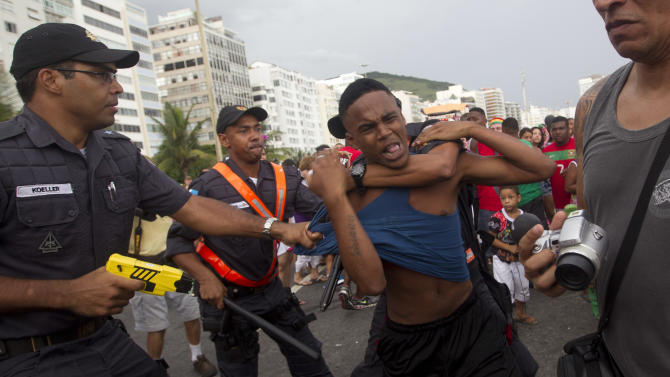 "Brazil's police officers detain an alleged thief during the ""Blocao"" dog carnival parade in Rio de Janeiro, Brazil, Sunday, Feb. 3, 2013. According to Rio's tourism office, Rio's street Carnival this year will consist of 492 block parties, attended by an estimated five million Carnival enthusiasts. (AP Photo/Silvia Izquierdo)"