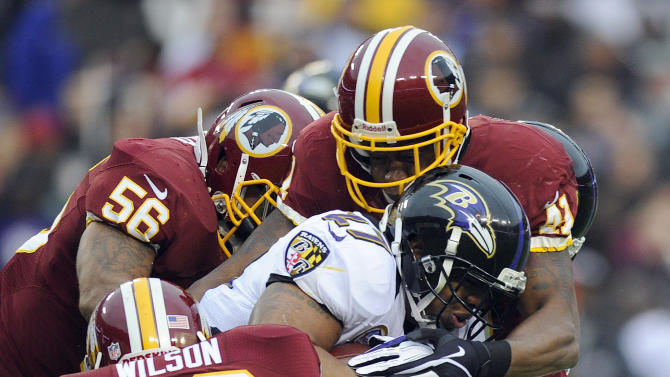 Baltimore Ravens running back Ray Rice is wrapped up by Washington Redskins cornerback Josh Wilson, inside linebacker Perry Riley (56) and free safety Madieu William (41) during the first half of an NFL football game in Landover, Md., Sunday, Dec. 9, 2012. (AP Photo/Nick Wass)