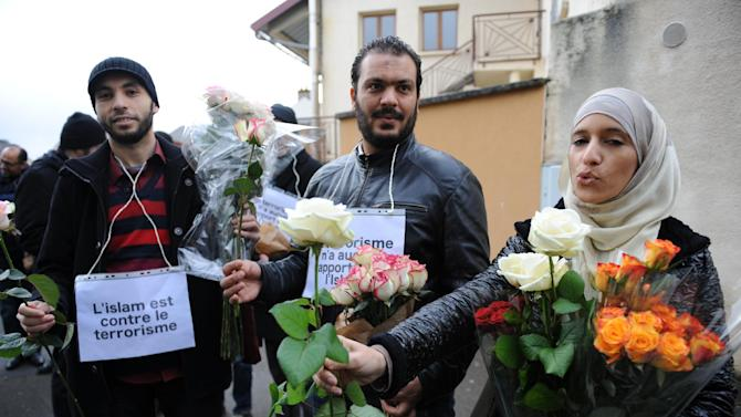 "Muslims with placards reading ""Islam is against terrorism"" offer roses in Le Mans, France, on January 10, 2015, in front of the mosque against which bullets were fired and 3 grenades launched on January 8"
