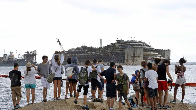 Youths look at and take pictures of the Costa Concordia cruise liner during its refloat operation at Giglio harbour