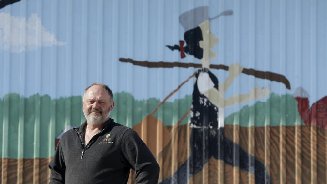 David Johnson poses in front of a Johnny Appleseed mural at his family's Apple Hills Farm on Thursday, Feb. 14, 2013, in Chenango, N.Y.  Johnson, who has a 30-acre pick-your-own apple farm on his mostly wooded 400 acres in Binghamton, said gas drilling money would allow him to replace some worn-out equipment like the tractor that he has to start with a screwdriver.(AP Photo/Mike Groll)