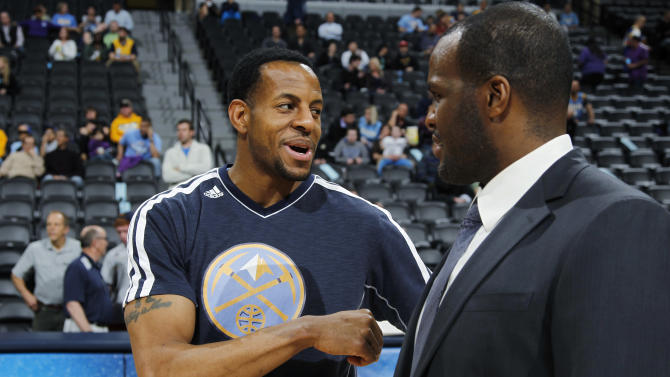 Denver Nuggets guard Andre Iguodala, left, who was acquired in an off-season trade last year from the Philadelphia 76ers, jokes with 76ers television analyst Malik Rose before the first quarter of an NBA basketball game in Denver, Thursday, March 21, 2013. (AP Photo/David Zalubowski)