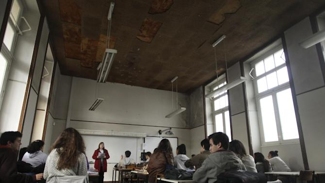 In this photo taken on March 11, 2013, Portuguese history teacher Maria Clara Melo da Silva, background, speaks to her students in a class-room of the Camoes high-school in Lisbon. The high school, one of the country's oldest and most prestigious, is a vivid demonstration of what happens when austerity is heaped on austerity. There are broken windows, cracked walls, flaking paint, ceilings stained by leaks, and sunscreens hanging off their hinges. (AP Photo/Francisco Seco)