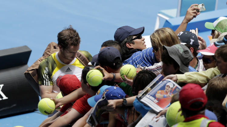 Britain's Andy Murray signs autographs following his win over Portugal's Joao Sousa in their second round match at the Australian Open tennis championship in Melbourne, Australia, Thursday, Jan. 17, 2013. (AP Photo/Rob Griffith)