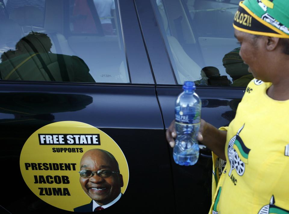 A supporter of the ruling party African National Congress (ANC) looks at a photo of her president Jacob Zuma pasted on a car door outside the venue of their elective conference at the University of the Free State in Bloemfontein, South Africa, on Monday, Dec. 17, 2012. (AP Photo/Themba Hadebe)