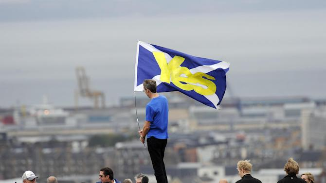 """A pro-independence supporter holds a Saltire flag with """"Yes"""" written on it in Edinburgh on September 21, 2013"""