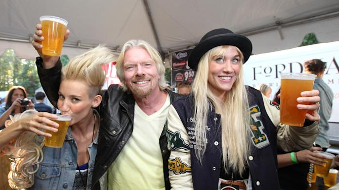 IMAGE DISTRIBUTED FOR VIRGIN MOBILE - Richard Branson, chairman and founder of Virgin Group Ltd., guest bartends with Olivia Nervo (L) and Miriam Nervo of Nervo at the 2012 Virgin Mobile FreeFest on Saturday, October 6, 2012 in Columbia, Maryland. (Photo by Paul Morigi / Invision for Virgin Mobile/AP Images)