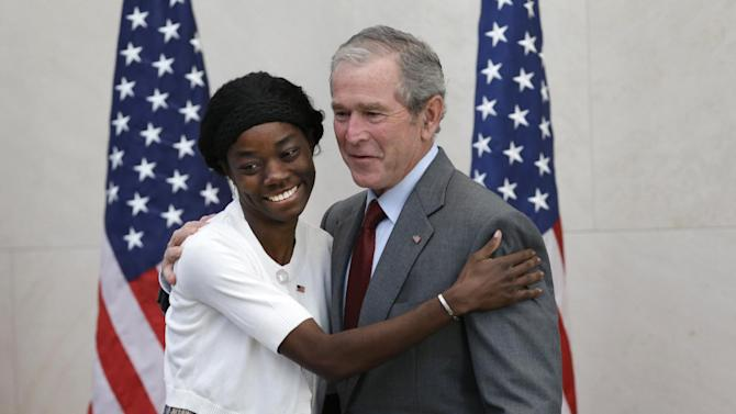 Former President George W. Bush, right, posses for a photo with Mondell Bernadette Avril after she was sworn in as a U.S. citizen during a ceremony at the The George W. Bush Presidential Center in Dallas, Wednesday, July 10, 2013. Twenty new citizens took the oath of U.S. citizenship at the former president's library. (AP Photo/LM Otero)