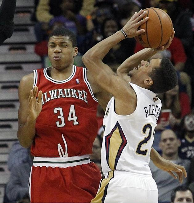 New Orleans Pelicans guard Brian Roberts (22) bumps into Milwaukee Bucks guard Giannis Antetokounmpo (34) during the first half of an NBA basketball game in New Orleans, Friday, March 7, 2014