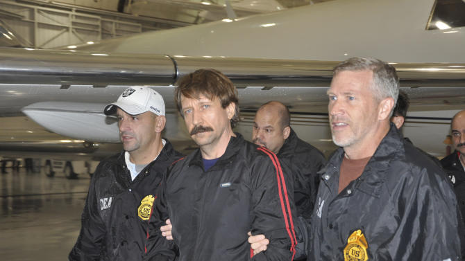 This image provided by the Drug Enforcement Administration shows Russian arms trafficking suspect Viktor Bout, center, in U.S. custody after being flown from Bangkok to New York on Tuesday Nov. 16, 2010 in a chartered U.S. plane, extradited in manacles to face terrorism charges despite a final outraged push by Russian diplomats to persuade Thailand to release him. (AP Photo/Drug Enforcement Administration)