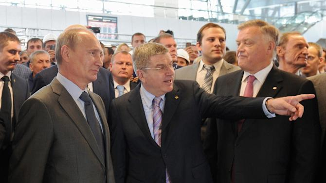 Russian President Vladimir Putin, left, listens to newly appointed IOC President Thomas Bach, center, during the opening ceremony of a railway station in Russia's Black Sea resort of Sochi, Monday, Oct. 28, 2013. International Olympic Committee president Thomas Bach has praised Russia's preparations for the Olympics, voicing confidence that the Winter Games in Sochi will be a success story. Bach met Monday with Putin in Sochi on his first trip there since taking office last month. Russian railway's chief Vladimir Yakunin stands at right. (AP Photo/RIA Novosti Kremlin, Mikhail Klimentyev, Presidential Press Service)