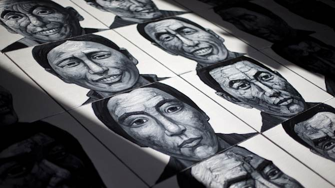In this photo taken on Tuesday, Dec. 25, 2012, portraits of Tibetans who have self-immolated over the past three years painted by Beijing-based artist Liu Yi are displayed at his studio in Songzhuang art village in Tongzhou, on the outskirt of Beijing. Liu is working on a series of black-and-white portraits he knows will never be shown in a Chinese gallery. His varied subjects - men and women, young and old, smiling and pensive - have one thing in common: They are Tibetans who have set themselves on fire to protest repressive Chinese rule. (AP Photo/Andy Wong)