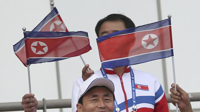 In this Sept. 18, 2014 photo, members of the North Korean delegation cheer their team during the men's first round Group F soccer match between North Korea and Pakistan at the 17th Asian Games at Hwaseong Sports Complex Main Stadium (AP Photo/Eugene Hoshiko)