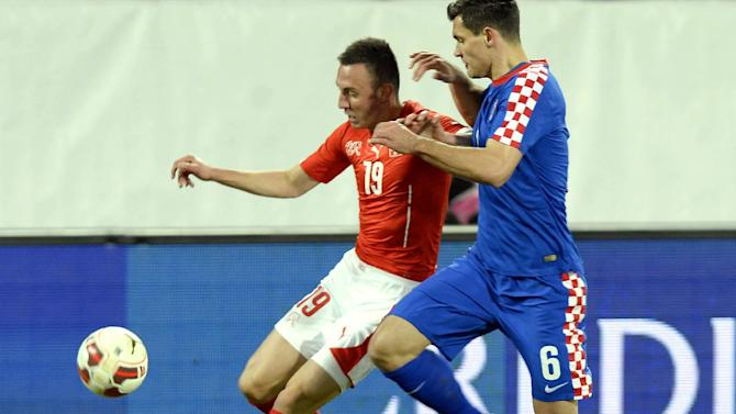 Swiss Josip Drmic, left,  challenges  for the ball with Croatia`s Dejan Lovren, right, during a friendly soccer match between Switzerland and Croatia at the AFG Arena in St. Gallen, Switzerland, Wednesday, March 5, 2014