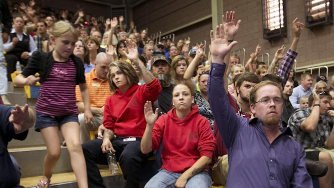 7/1/13 - Yarnell Hill Fire - Levi Weinberger, right, raises his hand with others to indicate he knew a firefighter that was killed during a memorial service for 19 firefighters of the Granite Mountain Hotshot Crew that were killed battling a wildfire, Monday, July 1, 2013 in Prescott, Ariz. (AP Photo/The Arizona Republic, David Wallace)