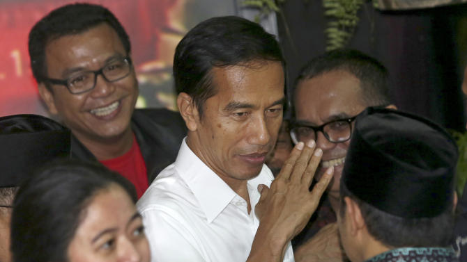 Presidential candidate Joko Widodo, center, gestures after a press conference in Jakarta, Indonesia, Tuesday, July 22, 2014. Jakarta governor Joko Widodo, who captured the hearts of millions of Indonesians with his common man image, won the country's presidential election with 53 percent of the vote, final results showed Tuesday. (AP Photo/Tatan Syuflana)