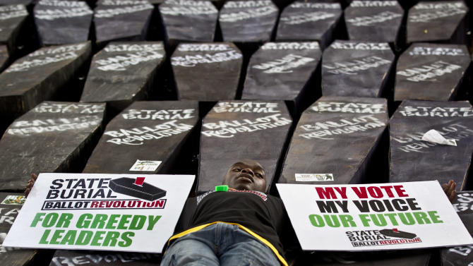 "FILE - In this Wednesday, Jan. 16, 2013 file photo, a demonstrator lies on mock coffins on which are written ""State Burial, Ballot Revolution"", before the coffins were carried to the Parliament and set on fire to protest against an attempt by Members of Parliament (MPs) to award themselves a $110,000 bonus, which was later vetoed by the president, in Nairobi, Kenya. Even before they begin their latest session in earnest, newly elected Kenyan parliamentarians are demanding a pay increase after the lavish wages legislators in the previous term earned were reduced, and one legislator even petitioned parliament on Thursday, April 18, 2013 to impeach members of the government commission that reduced their salaries. (AP Photo/Ben Curtis, File)"
