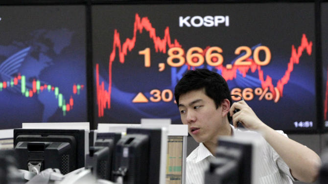 A currency trader works in front of a screen showing the Korea Composite Stock Price Index at the foreign exchange dealing room of the Korea Exchange Bank headquarters in Seoul, South Korea, Monday, June 11, 2012. South Korea's Kospi rose 1.71 percent, or 31.40 points, to close at 1,867.04. (AP Photo/Ahn Young-joon)