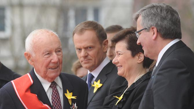Simha Rotem, left, one of the last living Warsaw Ghetto insurgents,  speaks in front of the Warsaw Ghetto Uprising memorial, speaks with Polish President Bronislaw Komorowski, right, as Polish Prime Minister Donald Tusk, second left, and Warsaw Mayor Hanna Gronkiewicz-Waltz listen, during the revolt anniversary ceremonies in Warsaw, Poland, Friday, April 19, 2013. Sirens wailed and church bells tolled in Warsaw as largely Roman Catholic Poland paid homage Friday to the Jewish fighters who rose up 70 years ago against German Nazi forces in the Warsaw ghetto uprising. (AP Photo/Alik Keplicz)